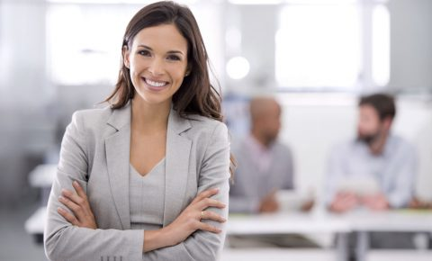 A woman in a business suit. She's smiling.