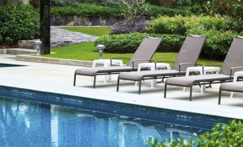 A large swimming pool with lounge chairs